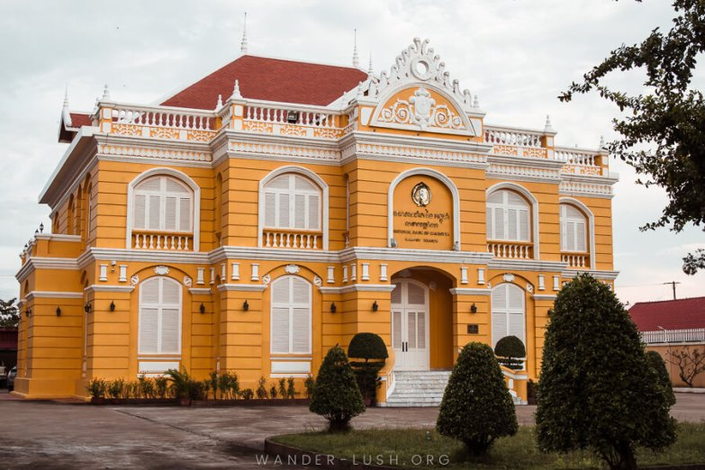 A beautiful yellow building with white detailing and manicured gardens.