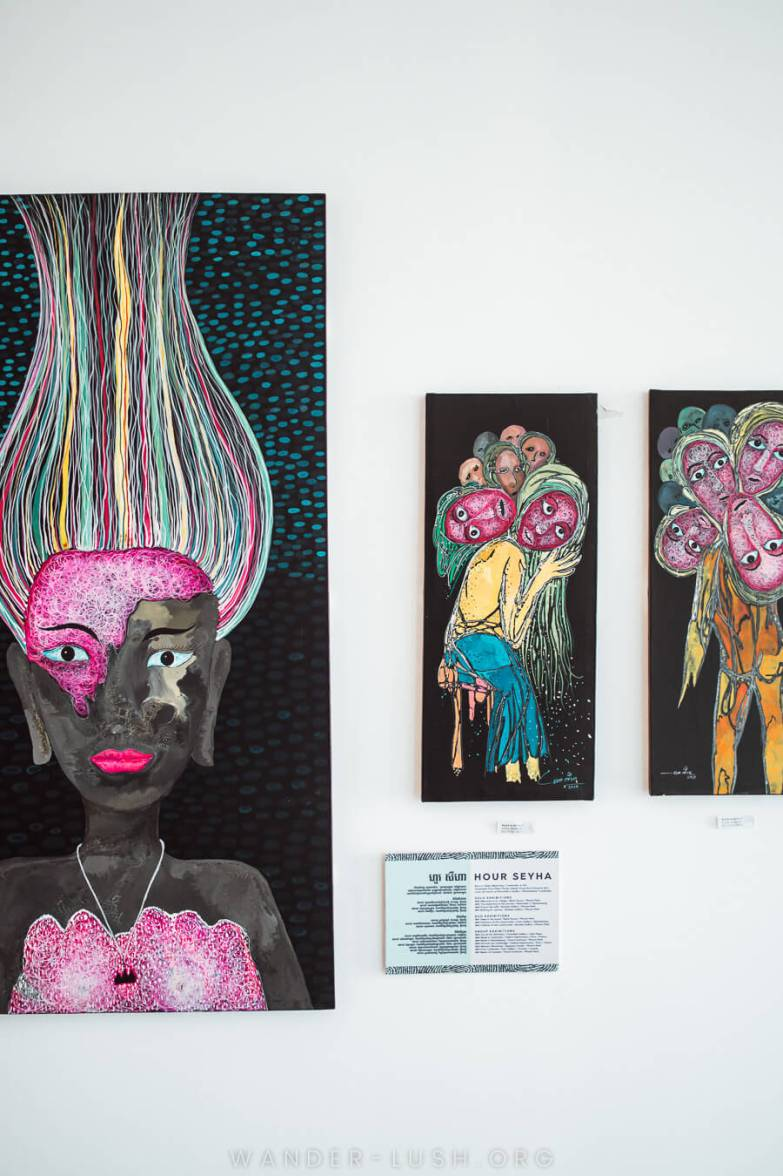Contemporary artworks hang on the white wall of a gallery in Kampot, Cambodia.