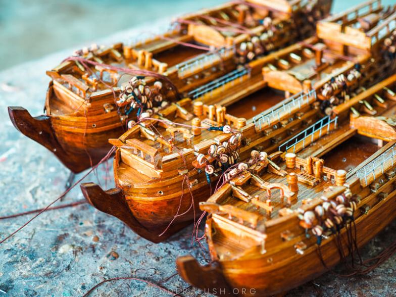 A row of wooden model ships sitting on a workbench.