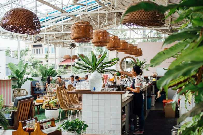 A trendy rooftop bar with leafy plants and large woven lampshades.