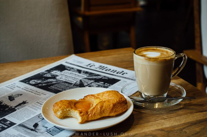 A cup of coffee and a danish sitting on a table with a copy of Le Monde newspaper.
