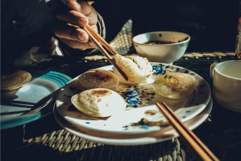 Eating rice pancakes with chopsticks.