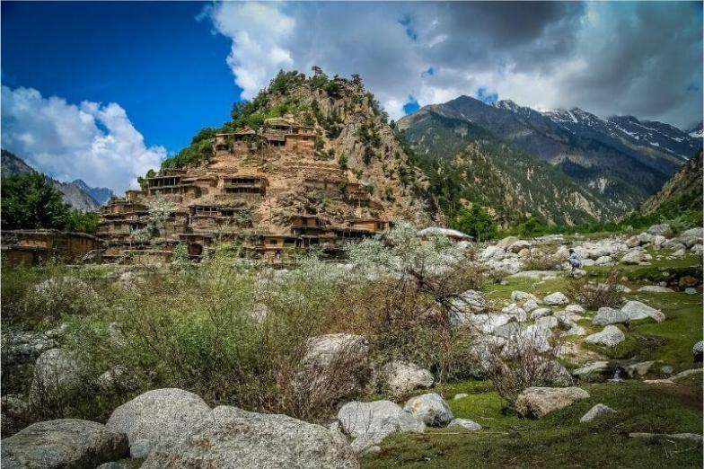 Wooden houses cling to the side of a hill in Pakistan.