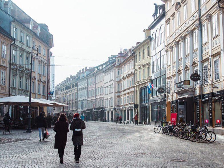 Two people walk down a pedestrian street in Ljubljana, Slovenia.