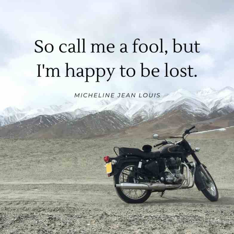 A motorbike sits in front of snow capped mountains.
