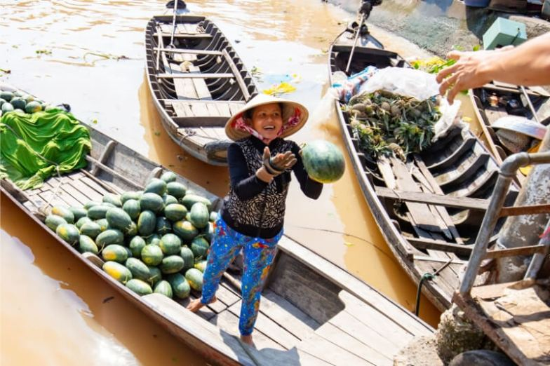 A woman wearing a conical hat and standing on a boat catches a watermelon.
