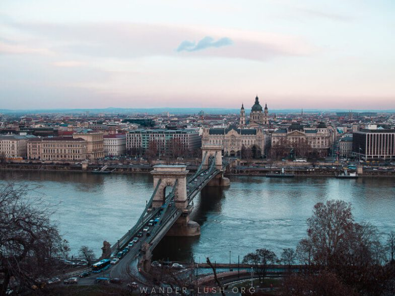 View of Budapest from above, with a grand bridge and river.