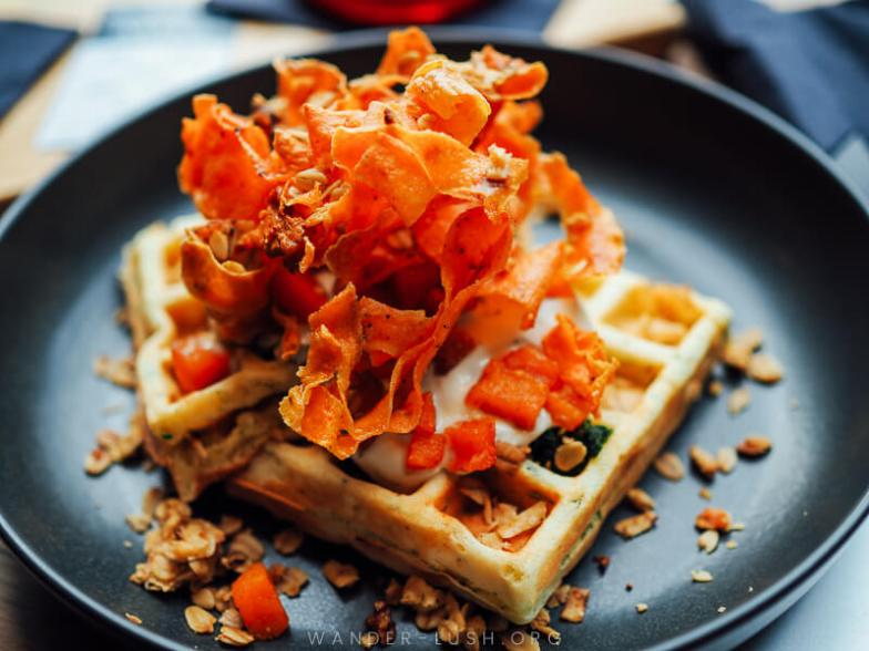 A waffle topped with shards of dried orange carrot.