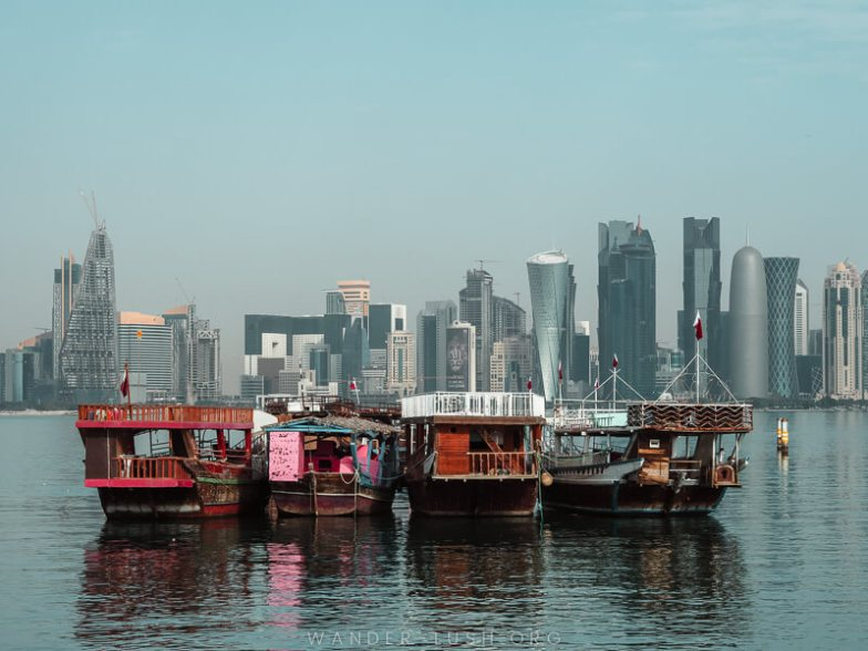 Wooden boats in front of a modern skyline in Doha, Qatar.