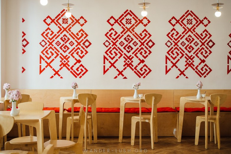 A beautiful cafe with white walls decorated with red stencils.