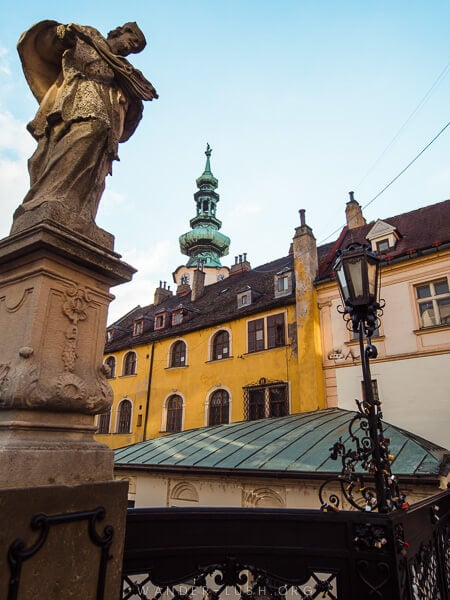 A statue overlooks a bridge and a set of colourful buildings in Bratislava.