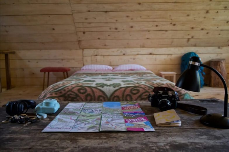 The interior of a wood cabin with a cosy bed and map spread out on a wooden desk.