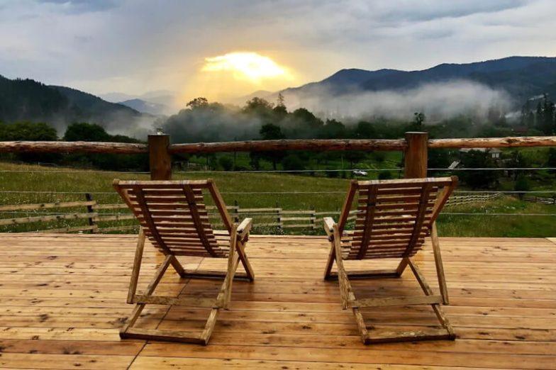 Two deck chairs on a wooden verandah overlooking a beautiful sunset.