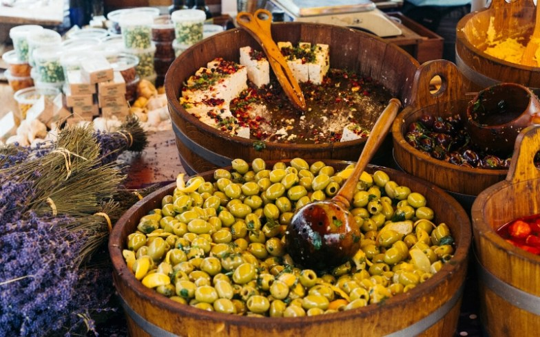 Wooden tubs of olives and cheese at a market in Athens.