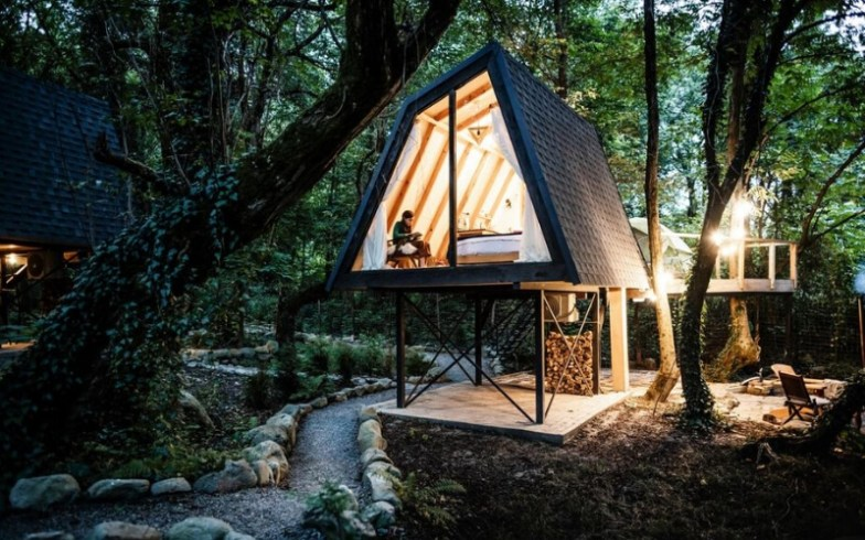 A contemporary cabin lit up at night in a forest in Georgia.