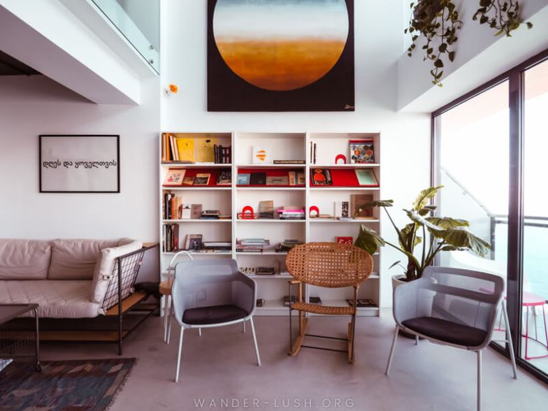 A modern loungeroom with a bookcase and contemporary artwork.