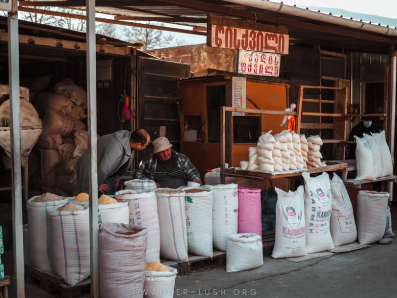 Market stands stacked with flour and grains.