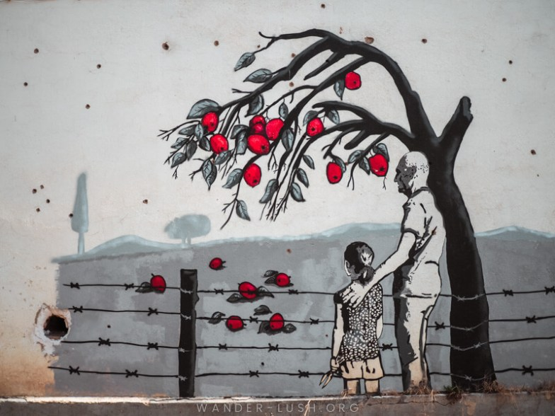 A wall mural depicts a man and child in front of an apple tree.