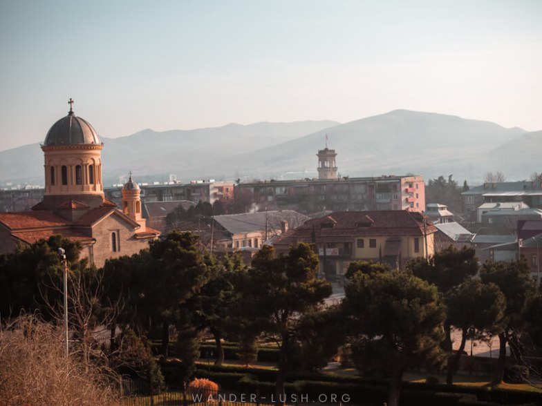A church bell tower and cityscape viewed in the early morning.