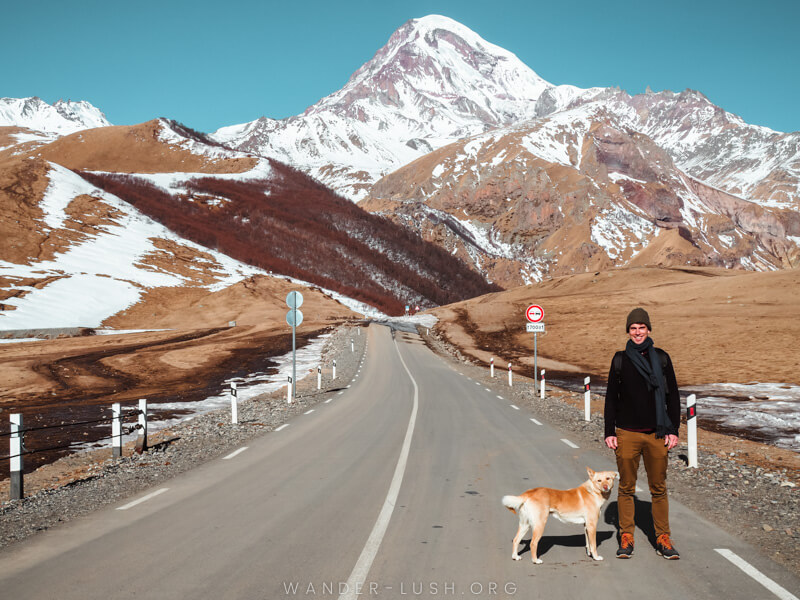 A man stands on a road in front of snow-capped mountains.