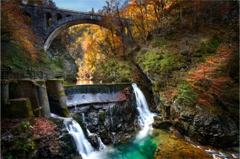 A beautiful stone bridge over a dam surrounded by autumn foliage.