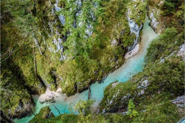 A blue river runs through a gorge in Europe.