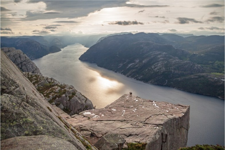 Two people stand on the edge of a flat rock overlooking a river gorge in Norway.