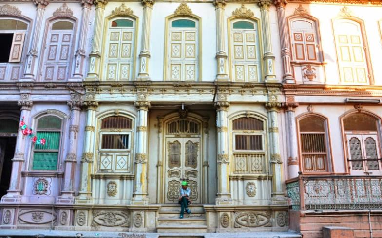 A woman sits in front of a row of colourfully painted buildings in Sidhpur, India.