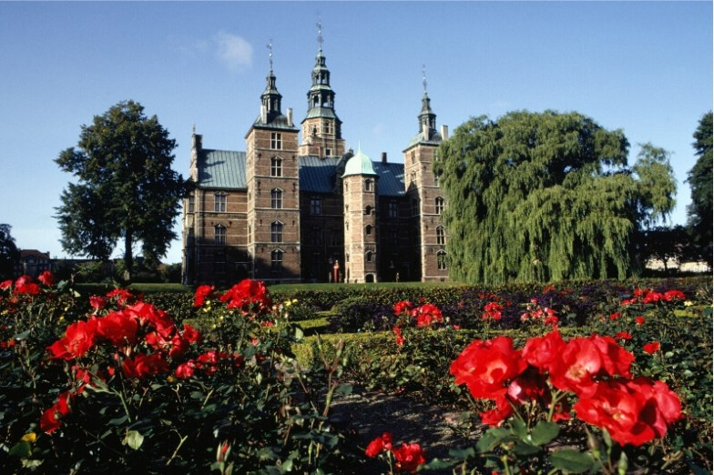 A beautiful Danish castle against a blue sky with red flowers in the foreground.