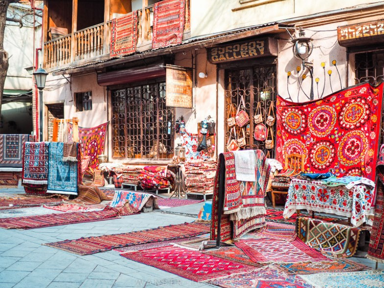 A carpet shop with dozens of colourful rugs out front and hanging from the walls.