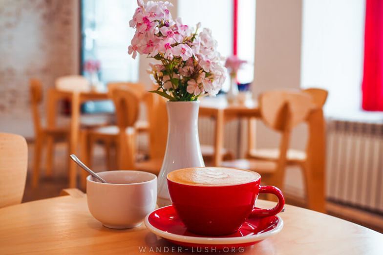 A red cup filled with coffee on a wooden cafe table with flowers in the background.