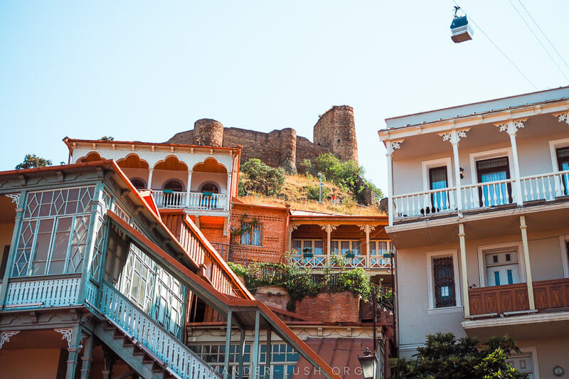 Beautiful Tbilisi buildings with balconies and Narikala stone fortress in the background.