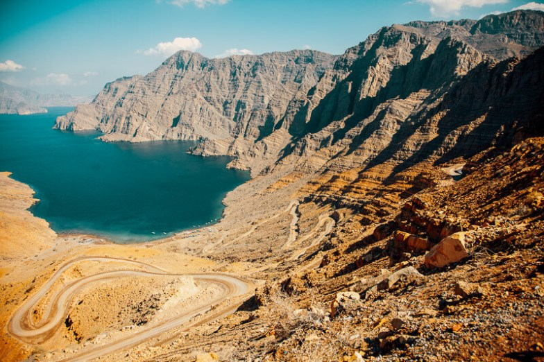 A dramatic landscape of mountains and cliffs, with a winding road leading to a blue bay.