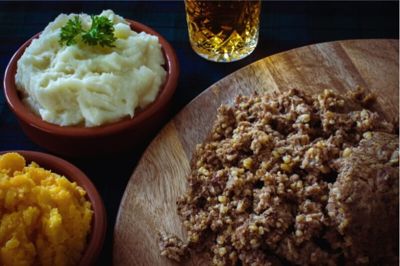 A spread of Scottish food, including haggis and mashed potatoes.