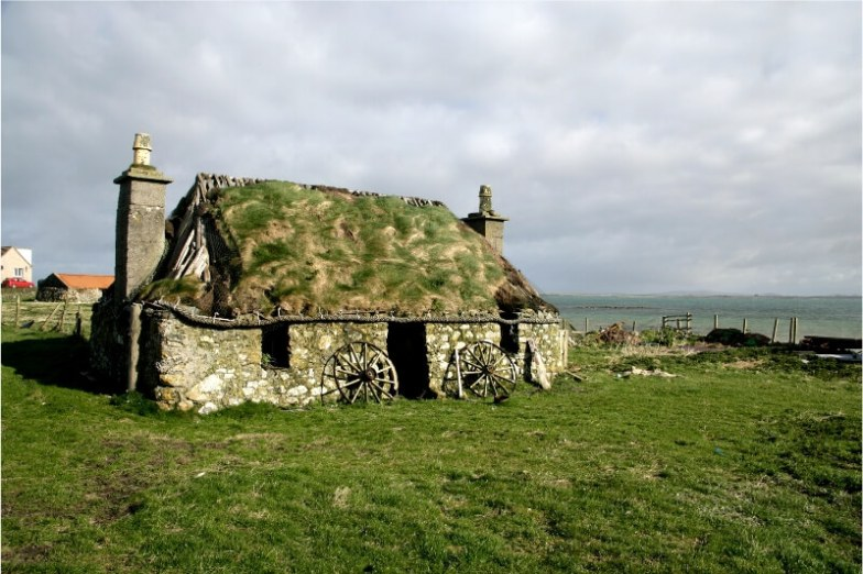 A stone cottage covered in moss.