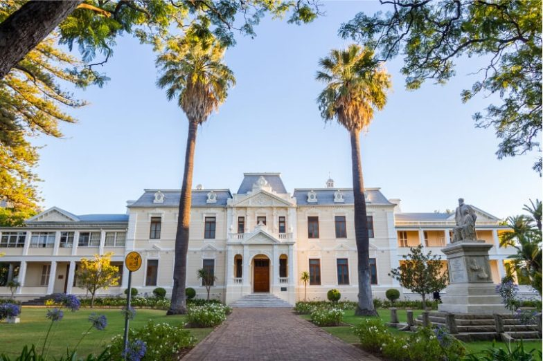 A beautiful heritage building in Cape Town surrounded by tall palm trees.