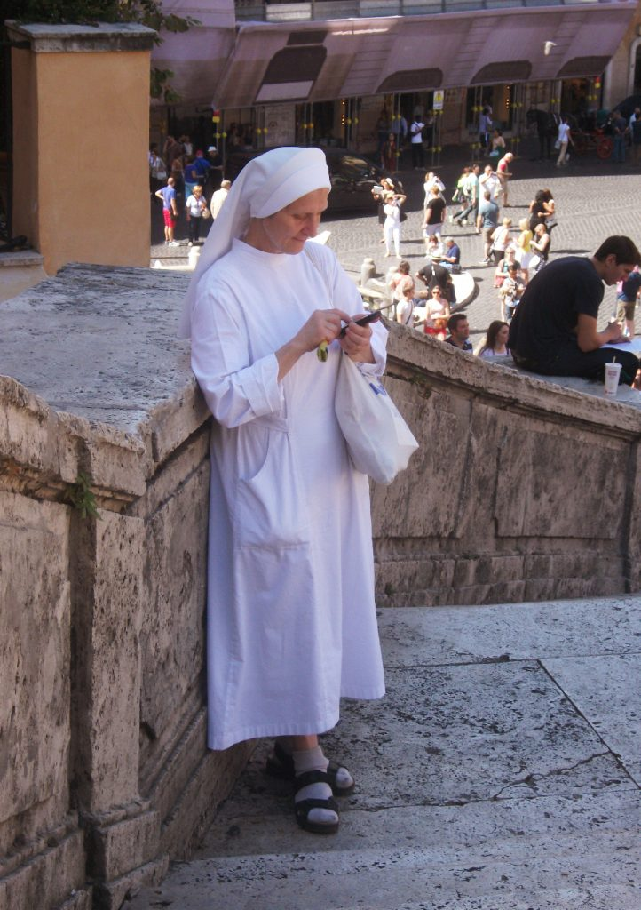 Nun texting on the Spanish Steps, Rome, Italy