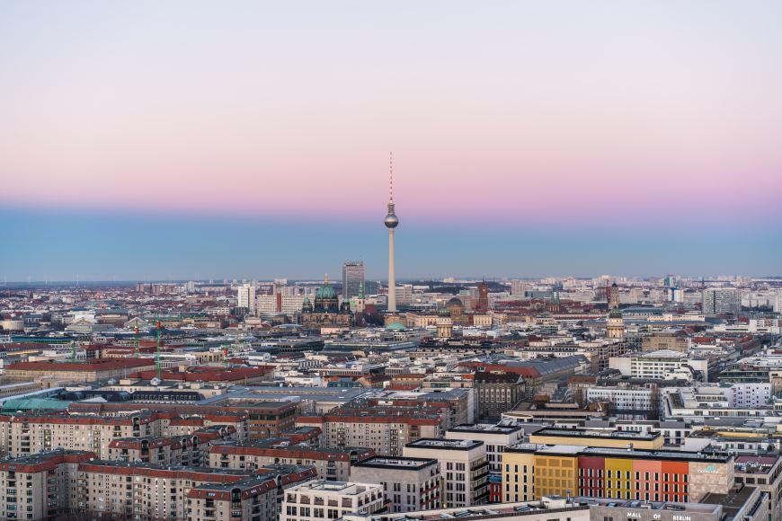 A view of the Berlin city skyline with the pink sunrise behind it