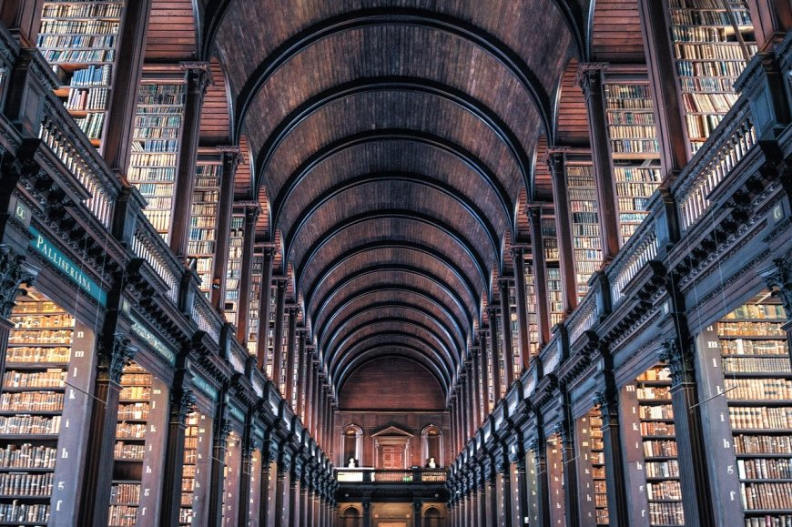 A wide angle photo of the library in Dublin with thousands of old brown books inside it