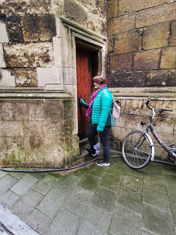 Justine opening an old wooden door in Ghent
