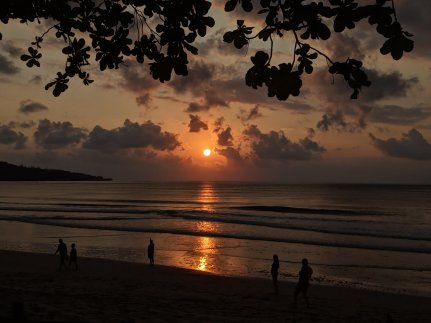 Jimbaran beach sunset with leaves border