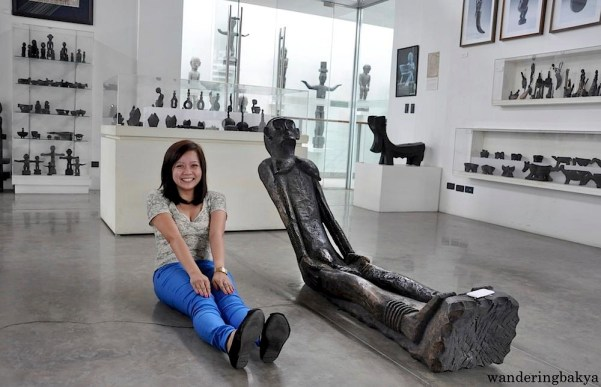 In a room full of sculptures