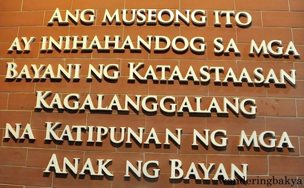 "Opposite the signage, a few feet above, is this dedication. In English it says, ""This Museum is dedicated to the heroes of the Supreme and Most Honorable (Society) of the Children of the Nation""."