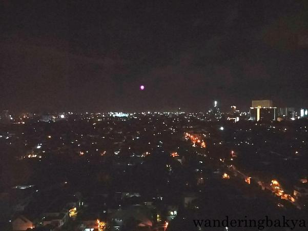 At night. I used my cellphone to take this photo. The moon was not red that night, the red object is the top of a tower somewhere in Quezon City.