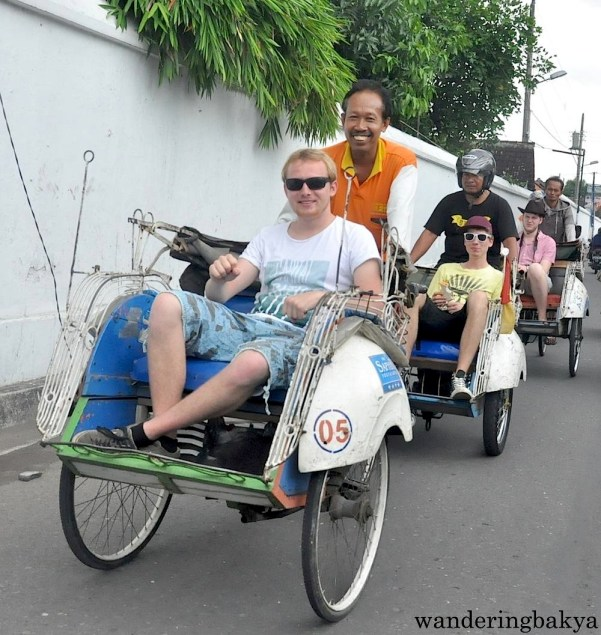 Foreigners riding becak in Yogyakarta.