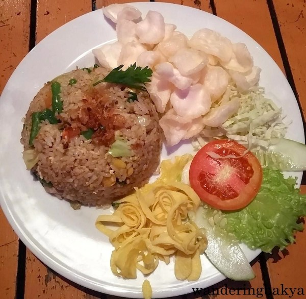 """Nasgor Sumringan, IDR 25,000 (US $1.95) at Raminten Resto and Cabaret Show, top floor of Mirota Batik. This was the hottest plate of Indonesian food I tasted on the trip. The waiter advised me to get the """"not spicy"""" version of this meal, but I told him """"medium spicy"""" (I do not know if there is such term). This innocent-looking plate of food arrived and I dug in immediately only to realize there was 2.5 long chili peppers chopped into smaller pieces and mixed with the rice. I finished my drink and had to order a bottle of water to (wrongly) alleviate the heat! Tears streamed down my cheeks and I had to almost lie down on the platform where we ate. The heat aside, the nasi goreng was packed with flavor."""
