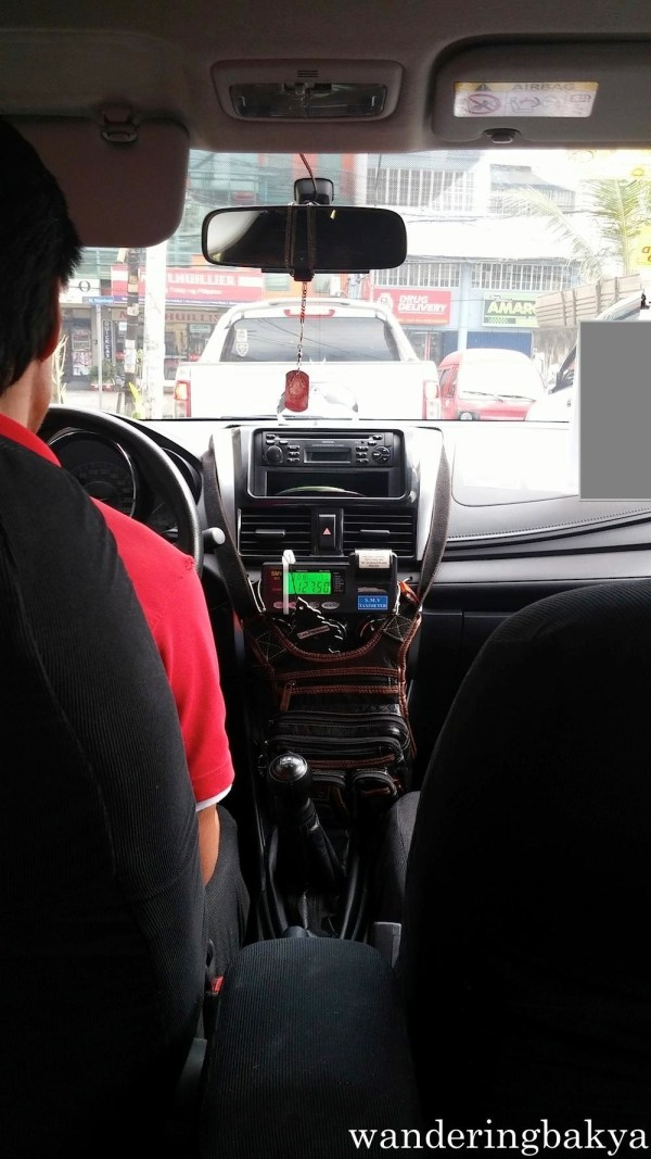 "Taxi in Metro Manila. Interior of taxi units include the ""No Smoking"" sign, cross or rosary beads and identification card of the driver (covered part on the upper right corner)."