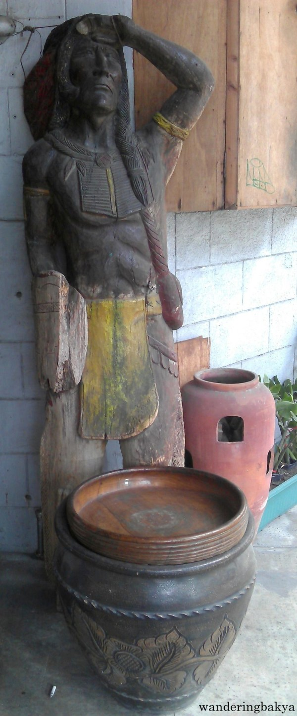 A carved man, around 6 foot-tall, and earthen jars, near the exit of Cubao Expo
