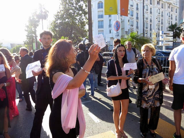 People holding invitation signs at Cannes