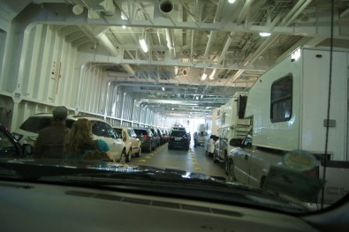 Cars and RV's are lined up inside the ferry
